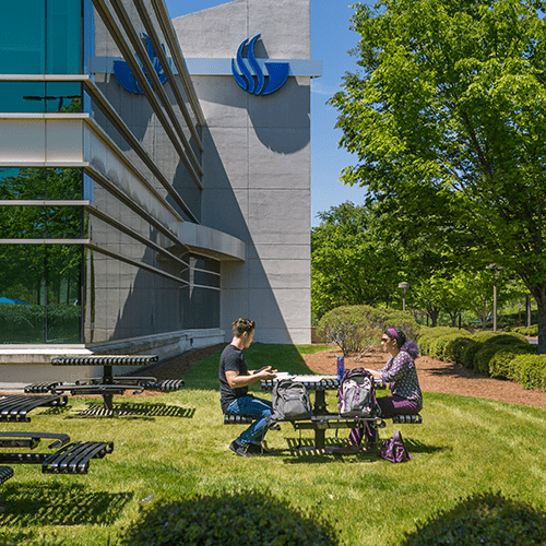 Male and female sitting at outdoor table beside building on alpharetta campus