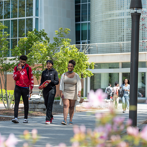 Two female and one african american male walking on sidewalk outdoors