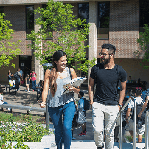 Female and Male student walking up stairs outdoors