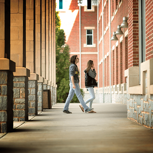 Male and Female student entering building on campus