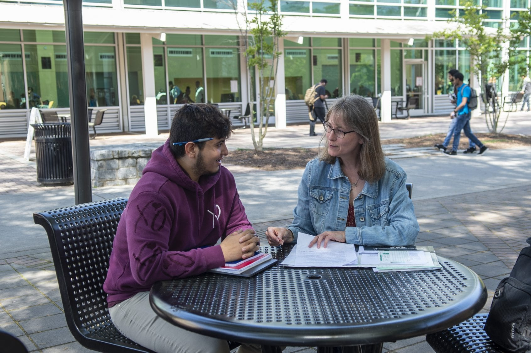 Male student sitting with female at outdoor round table
