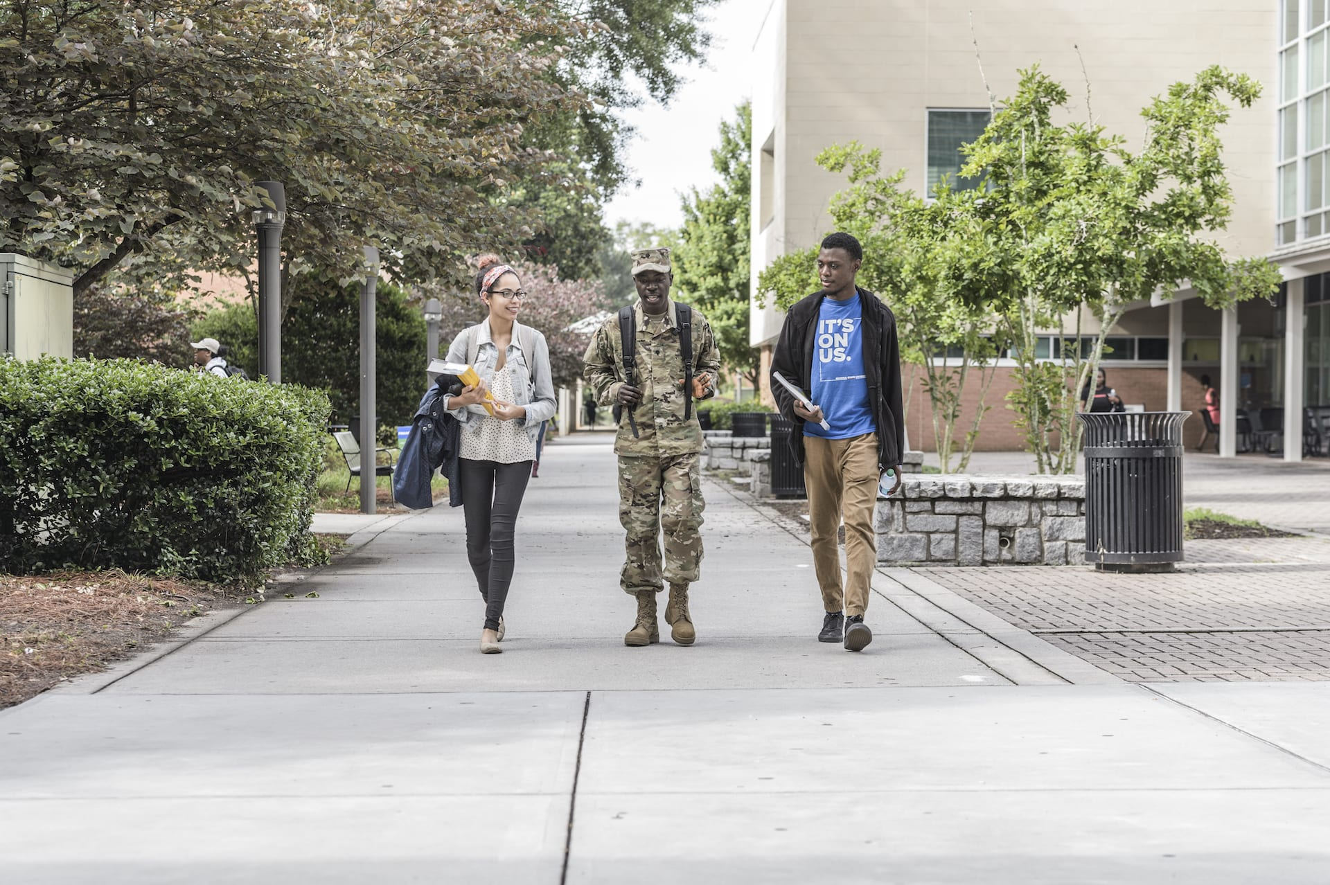 Two students and a student in military uniform walking down sidewalk